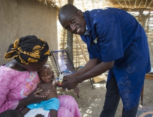 Famakan Kiabou, a Community Health Worker trained by Action Against Hunger in the remote village of Kourounan, Mali, screens a child for malnutrition. Photo: B.Stevens/i-Images for Action Against Hunger, Mali