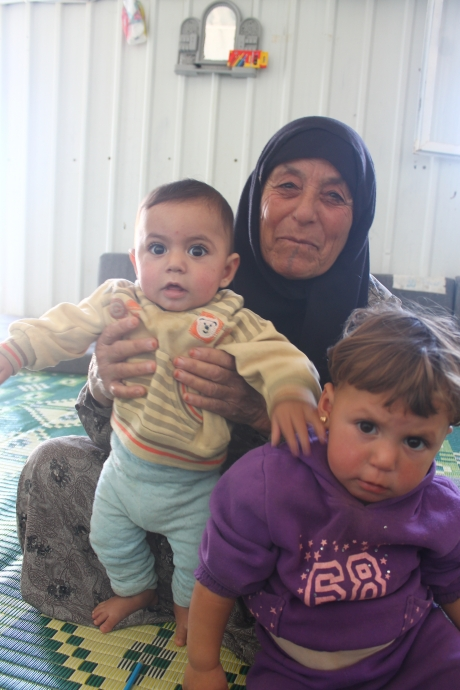 Amina holds two of her grandchildren, and hopes to be reunited with the rest of them.